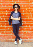 Fashion woman wearing a black rock style over bricks background Royalty Free Stock Image
