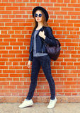 Fashion woman wearing a black rock style walking in city over bricks background. Fashion woman wearing a black rock style walking in city over bricks textured Royalty Free Stock Images