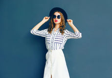 Fashion woman wearing a black sunglasses, hat and white skirt Royalty Free Stock Photos