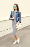 Fashion woman wearing a jeans jacket and striped dress Royalty Free Stock Images