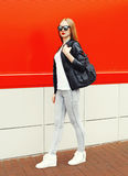 Fashion woman wearing a rock black jacket, sunglasses and bag walking in city over red Stock Images