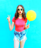 Fashion woman wearing a t-shirt, denim shorts with yellow air balloon over colorful blue. Background Stock Images