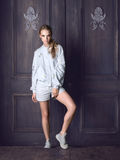 Fashion woman wearing white jacket, shorts and sneakers posing against door. Royalty Free Stock Image