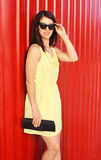 Fashion woman wearing yellow dress and sunglasses with handbag clutch over red Royalty Free Stock Photos