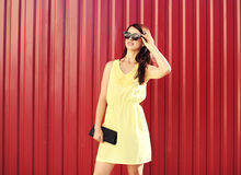 Fashion woman wearing a yellow dress and sunglasses with handbag clutch over red. Background stock photography