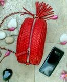Luxury red handmade snakeskin handbag, flowers frangipani, sunglasses, phone. Fashion women accessories.Python snake stock photo