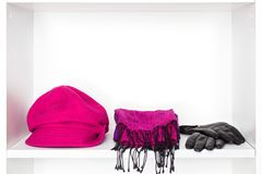 Fashion women accessories on white shelf in dressing room. Fashion women accessories. Wool cap magenta color, fringe scarf, black leather gloves on white shelf Royalty Free Stock Photography