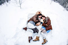 Fashion women lying on white snow winter background fisheye Royalty Free Stock Photo