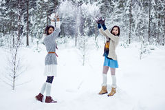 Fashion women in warm sweaters playing with snow on white forest background Stock Image