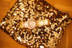 Fashion womens wristwatch on golden sequins sparkling sequined t Royalty Free Stock Photography