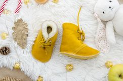 Fashion yellow genuine leather soft natural kids shoes.Newborn hand made real sheepskin Baby Slippers. Autumn winter. Concept flat lay composition. Stylish and royalty free stock image