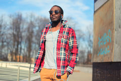 Fashion young african man listens to music in earphones outdoors wearing a plaid red shirt and sunglasses street stock photos