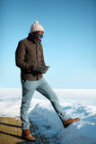 Fashion young african man listens to music on smartphone over blue sky in cold winter Royalty Free Stock Photography