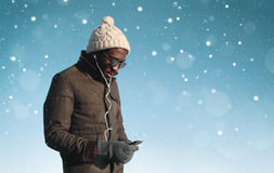 Fashion young african man listens to music on smartphone in winter day Stock Photo