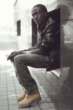 Fashion young african man sitting in the city Royalty Free Stock Image