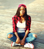 Fashion young african woman is having fun in the city, wearing a red checkered shirt baseball cap. Fashion young african woman is having fun in the city, wearing Stock Photo