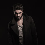 Fashion young bearded man wearing long coat with big collars. Fashion young man with beard wearing long coat with big collars looking at the camera Royalty Free Stock Photos