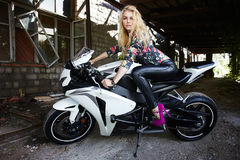 Fashion young blond woman on a sport motorcycle. Outdoor lifestyle portrait of sexy biker girl sitting on a sport motorcycle.fashion young blond woman Stock Photography