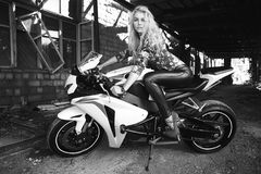 Fashion young blond woman on a sport motorcycle. Outdoor lifestyle portrait of sexy biker girl sitting on a sport motorcycle.fashion young blond woman.black and Royalty Free Stock Photo