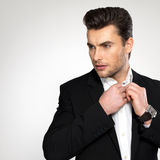 Fashion young businessman in black suit. Fashion young businessman black suit casual  poses at studio Royalty Free Stock Photos