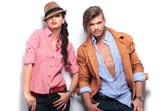 Fashion young couple posing with hands in pockets. Against white studio wall Royalty Free Stock Photos