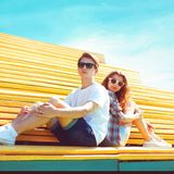 Fashion young couple sits on the bench city park at sunny summer day stock images