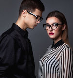 Fashion young couple in trendy glasses and stlylish clothes over. Dark grey background Royalty Free Stock Image