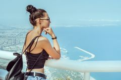 Beautiful young tourist girl with backpack near sea. Fashion young girl with backpack in casual clothes glasses enjoying a view from the mountain to the sea royalty free stock images