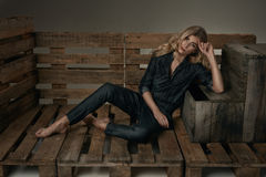 Fashion young girl with beautiful long blond hair lying on a woo Royalty Free Stock Photography