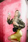Fashion young girl blogger dressed in a stylish black and yellow jacket and yellow shorts takes a selfie on the. Smartphone possing on the background of pink royalty free stock photo