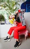 Fashion young girl blogger dressed in stylish striped jacket and red trousers poses sitting on the stool with pink fur stock photography