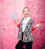 Fashion young girl blogger dressed in stylish striped shirt and red trousers poses on the background of pink fur wall royalty free stock photo