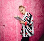 Fashion young girl blogger dressed in stylish striped shirt and red trousers poses on the background of pink fur wall stock images