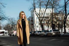 Fashion young girl in glasses. Blonde, red lips, beige coat walking along the city street. Fashion, stylish girl with a hipster hairdo. Creative person Royalty Free Stock Photo