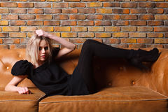 Fashion young girl on leather sofa Royalty Free Stock Photo