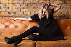 Fashion young girl on leather sofa Stock Image