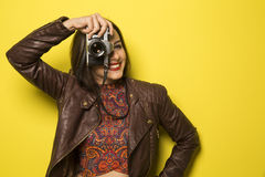 Fashion young girl makes the photo with old camera. Yellow backg Stock Image
