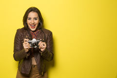 Fashion young girl makes the photo with old camera. Yellow backg Stock Photo