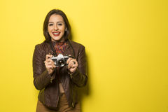 Fashion young girl makes the photo with old camera. Yellow backg Royalty Free Stock Image