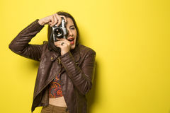 Fashion young girl makes the photo with old camera. Yellow backg Royalty Free Stock Photography