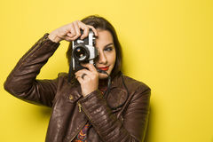 Fashion young girl makes the photo with old camera. Yellow backg Stock Photos