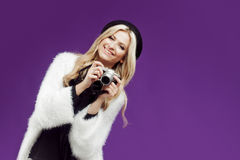 Fashion young girl makes the photo. Purple background. Photographer stock photo
