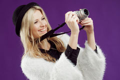 Fashion young girl makes the photo. Purple background. Photographer stock image