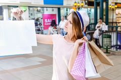 Fashion young girl portrait. Beauty Woman with craft paper bags in Shopping Mall. Shopper. Sales. Shopping Center. Space for text. Stock Photo