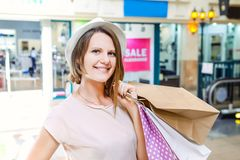 Fashion young girl portrait. Beauty Woman with craft paper bags in Shopping Mall. Shopper. Sales. Shopping Center. Space for text. Stock Image