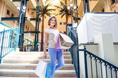 Fashion young girl portrait. Beauty Woman with craft paper bags in Shopping Mall. Shopper. Sales. Shopping Center. Space for text. Royalty Free Stock Photo
