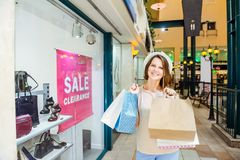 Fashion young girl portrait. Beauty Woman with craft paper bags in Shopping Mall. Shopper. Sales. Shopping Center. Space for text. Royalty Free Stock Image