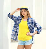 Fashion young girl wearing a cap and checkered shirt Royalty Free Stock Photography