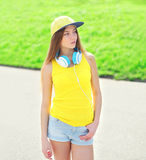 Fashion young girl wearing a cap, headphones and t-shirt Stock Photo