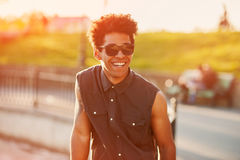 Fashion young male wearing sunglasses. Curly stylish handsome african american young man smiling at sunset with sunlight effect. Teenage lifestyle concept Royalty Free Stock Photography
